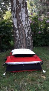Berbera Design- collection Atlas- coussins avec housses berbera- empilées et posés sur l'herbe devant un arbre