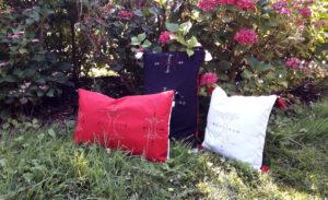 Berbera Design- collection Atlas-coussins avec housses coussin Berbera - posés dans la nature sur l'herbe- devant des fleurs