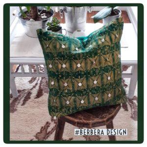 Berbera Design - coussin avec housse de coussin Tazmurt Luciole- mis sur un tabouret en bois posé sur un tapis berbère