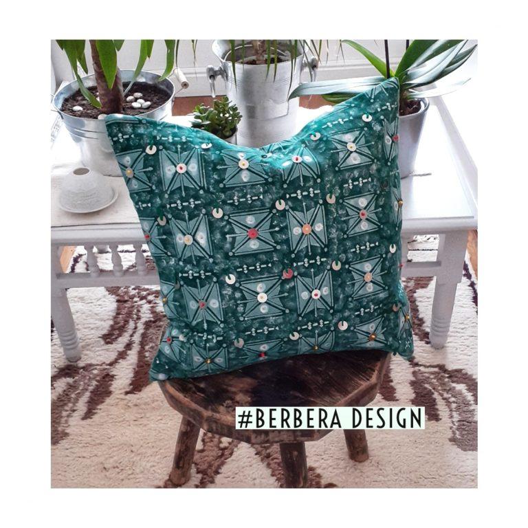 Berbera Design - capsule Tazmurt Perle-coussin avec housse de coussin 40x40 - mise en situation sur un tabouret posé sur un tapis berbère-devant une table sur laquelle sont posées des plantes