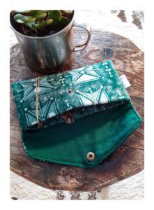 Berbera Design- Pochette Tazmurt Perle- ouverte et posée sur un tabouret en bois -