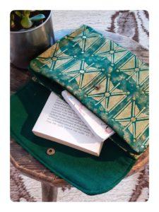 Berbera Design- Pochette Tazmurt Luciole - ouverte avec un livre et posée sur un tabouret en bois
