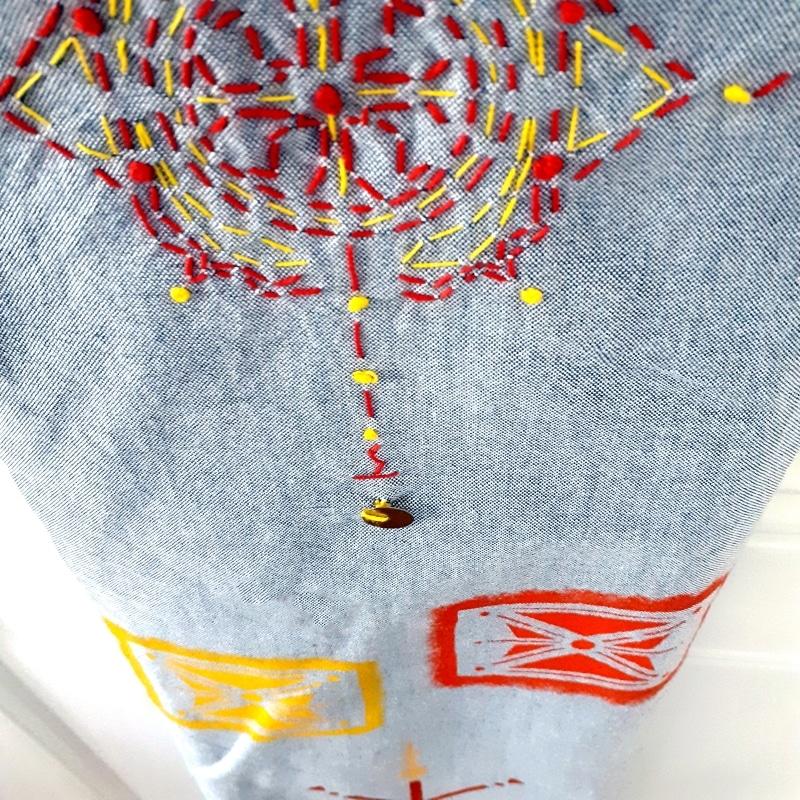 Berbera Design détail motif brodé et peint - rouge jaune sur tissu gris